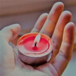 lit reddish tea candle in hand