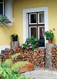 Large stack of firewood against yellow house